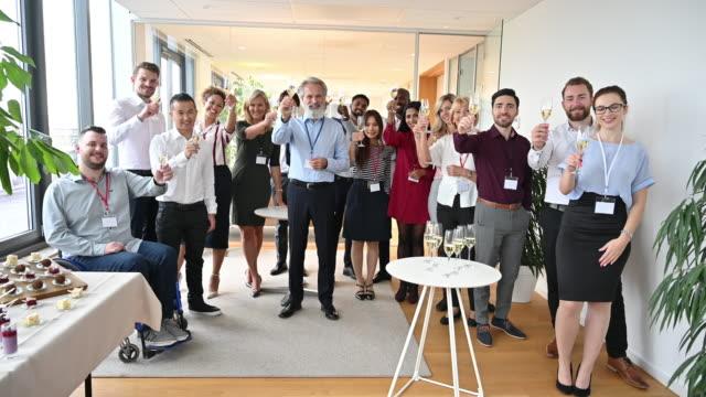 ceoと多様なビジネスチームがシャンパントースト用グラスを持ち上げる - disabilitycollection点の映像素材/bロール