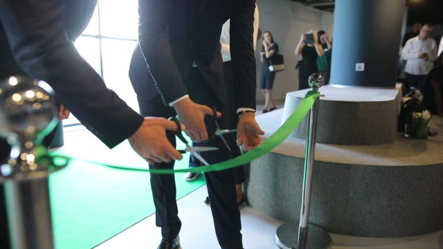 CEO and his assistant cutting a green ribbon at opening ceremony. They are starting a new business