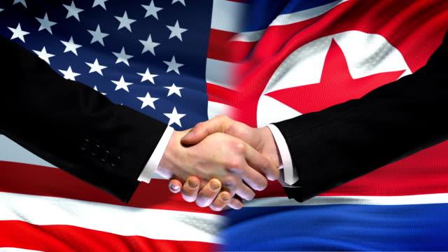 vidéos et rushes de etats-unis et corée du nord poignée de main, l'amitié internationale, drapeau fond - nord