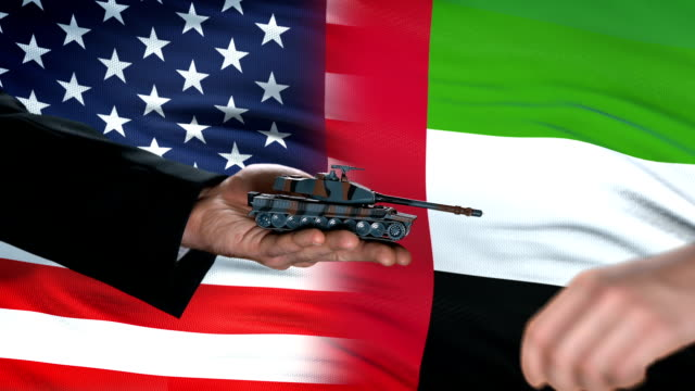 USA and UAE officials exchanging tank for money on flag background, partnership video