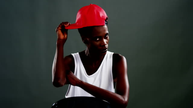 androgynous man posing with red cap - кепка стоковые видео и кадры b-roll