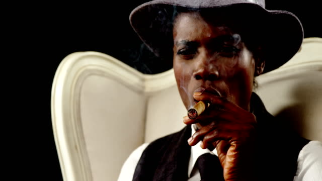 uomo androgino che fuma sigaro sulla poltrona - sigaro video stock e b–roll