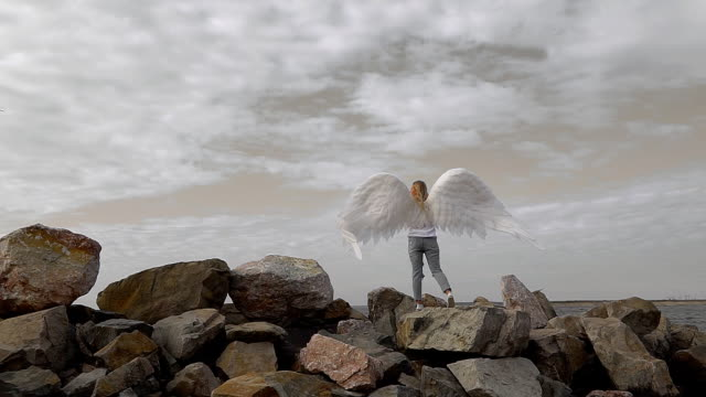 Angel girl with white wings stands on stones and looks into the sky FHD