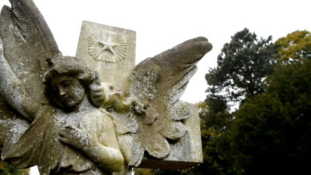 Angel statue and cross, with camera move. Camera moves to frame a weathered statue of an angel. 19th century style stock videos & royalty-free footage