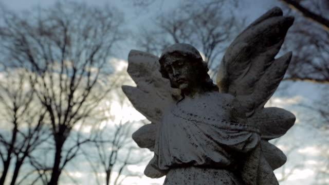 statua di angelo bellissima sole al tramonto con flare rallentatore - statua video stock e b–roll
