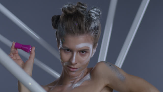 vidéos et rushes de modèle angélique haute couture dans le maquillage de scène détient la bouteille de vernis à ongles rose. mode vidéo. - crayon à lèvres