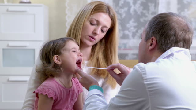 Angina. A pediatrician examines the throat of a little girl. video