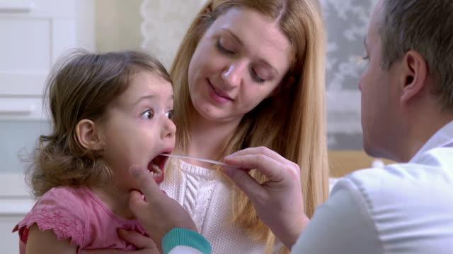 angina. bir pediatrist küçük bir kızın boğazını inceliyor. - ziyaret stok videoları ve detay görüntü çekimi