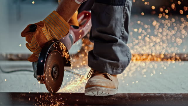 slo mo angle grinder causing sparks when cutting through metal pipe - inarcare la schiena video stock e b–roll