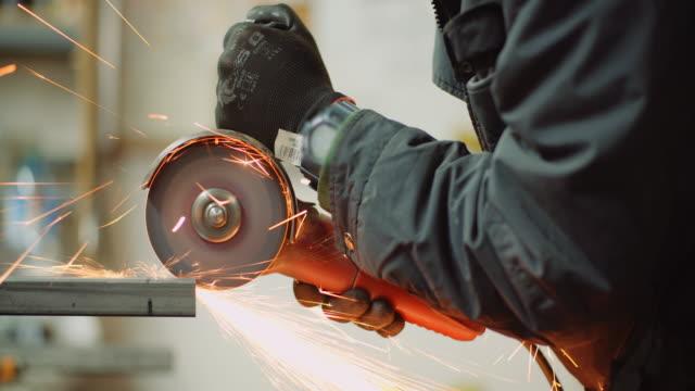 vídeos de stock e filmes b-roll de angle grinder cutting metal at workshop - triturar atividade