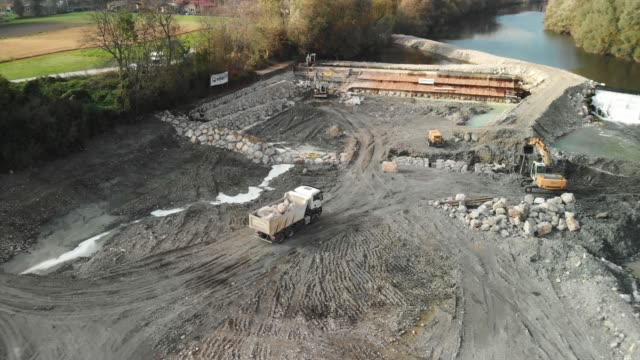 Angle view of a truck driving on to dam construction site Dam construction site in progress, angle view from the air of a truck fully loaded with rocks, driving on to construction site. crane construction machinery stock videos & royalty-free footage
