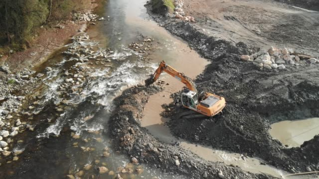Angle view of excavator building a temporary dam on the river strem Excavator digging a pit, changing the river bed natural path. Zoom in shoot of an excavator at construction site of a dam. crane construction machinery stock videos & royalty-free footage