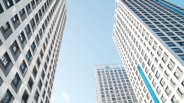 Angle view of white skyscrapers against blue sky. Frame. Fantastic below view