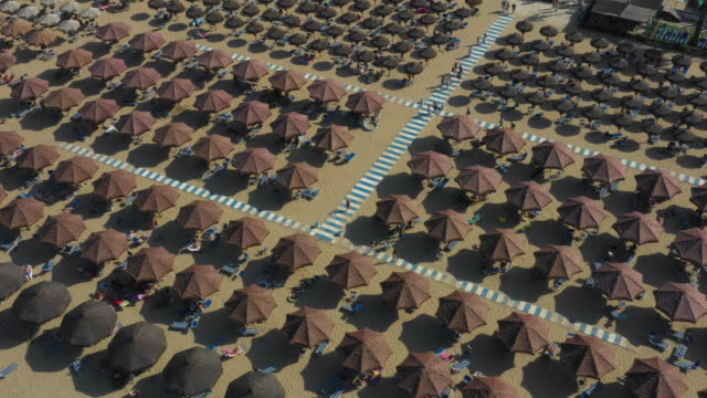 Angled Aerial Shot Of Brown Beach Umbrellas And Striped Walkways On Italian Beaches Filled With People Relaxing Under The Sun