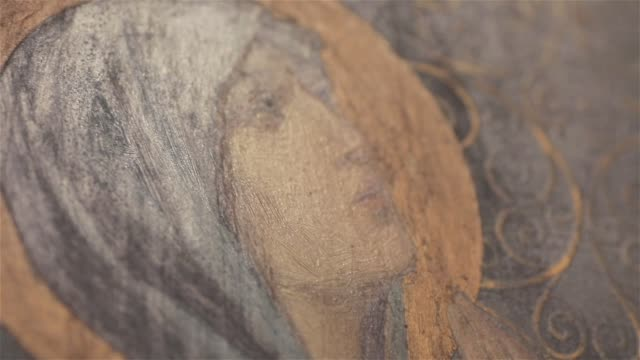 Angled detail of icon image of Virgin Mary in St Nicholas Orthodox Cathedral in Nice France macro close up light moving. Oil painting of Mother of God look with signs of brush marks video