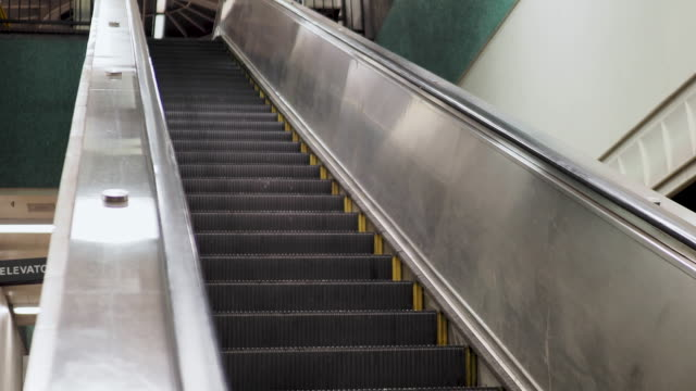 angled shot of escalator going down in underground subway station - escalator video stock e b–roll