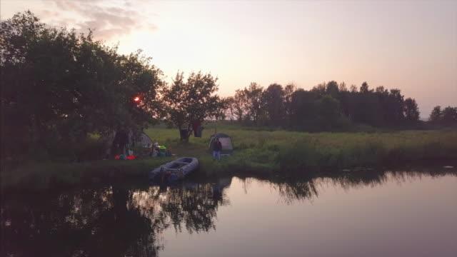 angler angeln von der küste des sees während des ruhigen sonnenuntergangs - angelhaken stock-videos und b-roll-filmmaterial