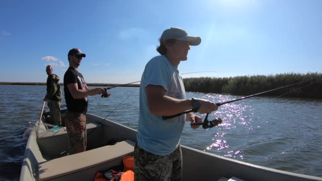 vídeos de stock e filmes b-roll de anglers fishing from the boat - pesca