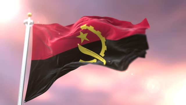 Angola flag waving at wind in slow at sunset, loop video