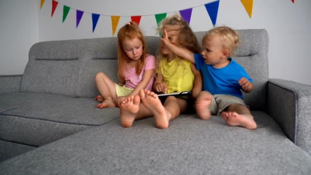 怒っている中毒性の子供たちはタブレットコンピュータで遊ぶために戦う。カメラの動き - 兄弟姉妹点の映像素材/bロール