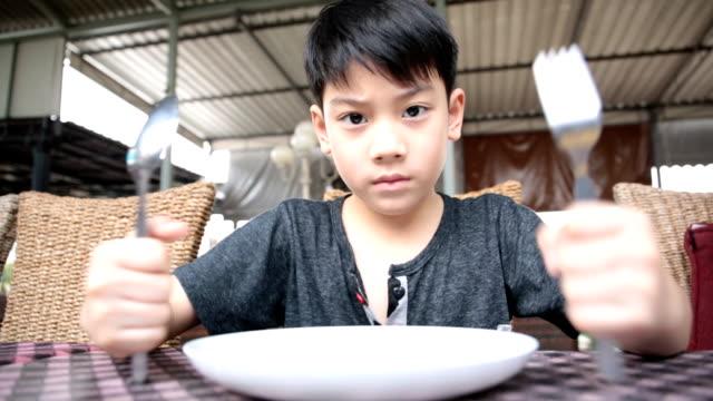 angry asian child waiting food for launch . - empty plate bildbanksvideor och videomaterial från bakom kulisserna