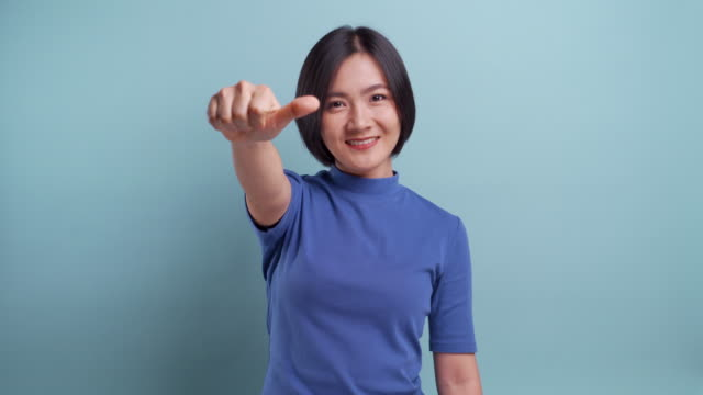 Angry asian woman looking at camera and show thumb up to down standing isolated on blue background. 4K video video