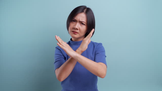 Angry asian woman looking at camera standing isolated on blue background. 4K video video