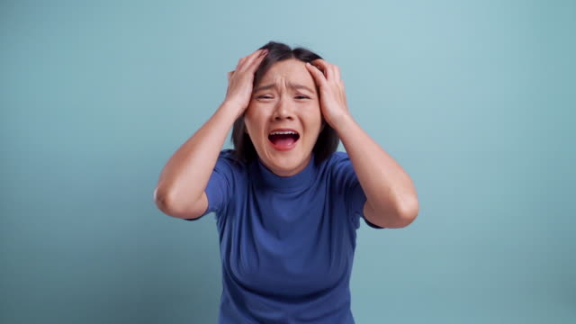Angry asian woman looking at camera standing isolated on blue background. slow motion video video