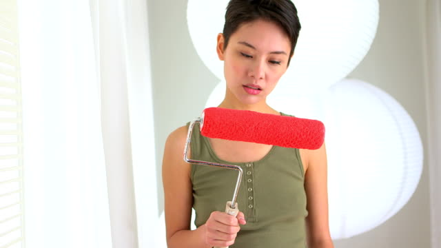 Angry Asian woman with paint roller in hand video