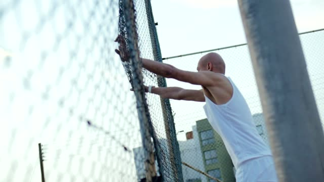 Angry bald man beats his hands on a grid fence. Aggressive young man video