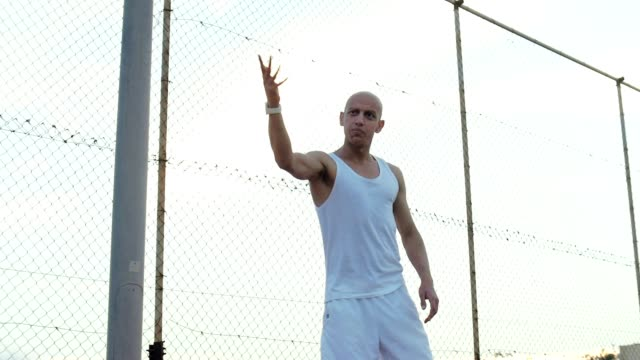 Angry bald man on background mesh fence. Bad guy from a poor neighborhood video