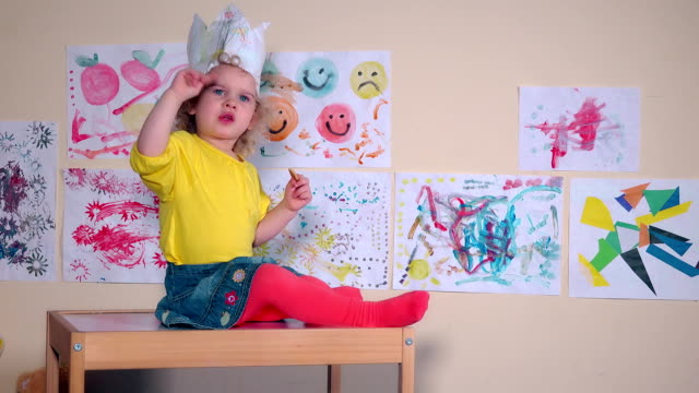 Angry beautiful kid eating cookie sitting on table against paintings on wall video