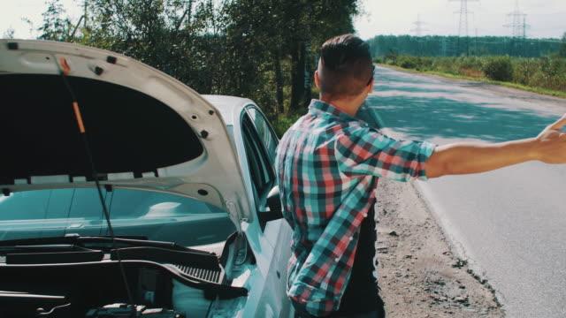 Angry boy stay at broken car at road. Hitchhiking. Waiting for help. Thumb up video