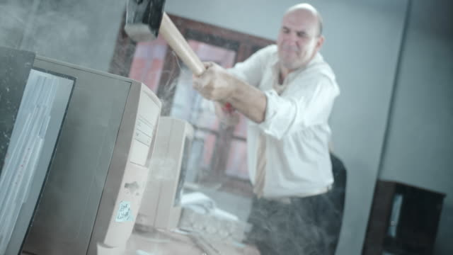 SLO MO Angry business man destroying his computer with hammer video