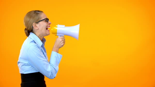 Angry business woman shouting in megaphone on orange background, leadership Angry business woman shouting in megaphone on orange background, leadership megaphone stock videos & royalty-free footage