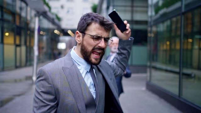 злой бизнесмен спорит со старшим генеральным директором после того, как он столкнулся с ним - гнев стоковые видео и кадры b-roll