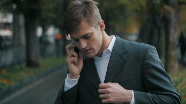 Angry businessman talking on the mobile phone. Upset business man. Handsome guy speaks, nervous and shouts into the phone in autumn street. Slow motion video