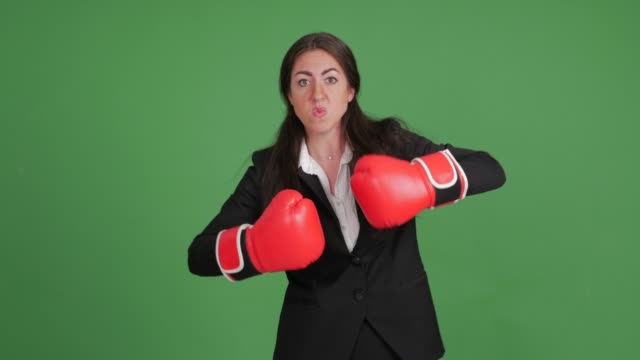 angry businesswoman in boxing gloves on a green background video