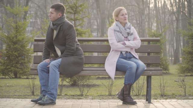 wütender kaukasischer mann und frau sitzen zurück zu hinten auf gegenüberliegenden seiten der bank im freien. unglückliches paar mit altersunterschied im stadtpark argumentiert. beziehungsprobleme, ehe - rücken an rücken stock-videos und b-roll-filmmaterial
