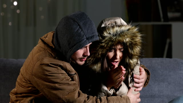 Angry couple freezing at home in a cold winter Cold home with an angry couple warmly clothed hugging sitting on a sofa in the living room at home in the night freezer stock videos & royalty-free footage