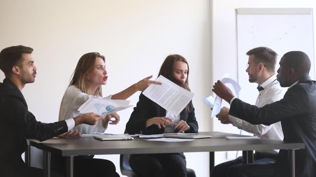 vídeos de stock e filmes b-roll de angry diverse team colleagues argue over paperwork during company meeting - brigar