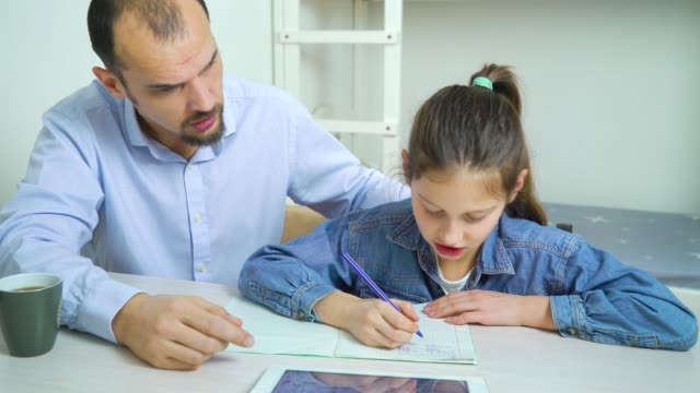 angry father is annoyed with his daughter doing homework