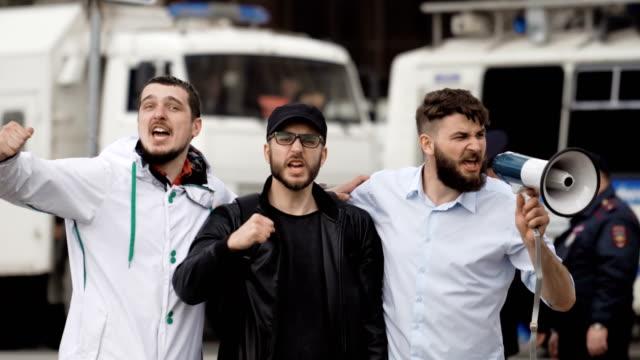 vídeos de stock e filmes b-roll de angry football fans scream on street in a megaphone. caucasian people on strike. - soccer supporter portrait