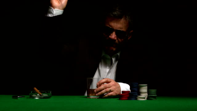 Angry gambler folding his hand of poker video