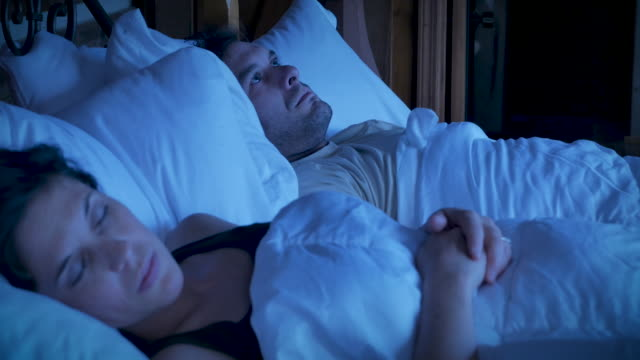 angry, irritated man lying in bed next to a sleeping woman at night - fare la lotta video stock e b–roll