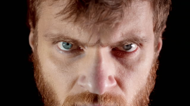 arga utseende av en ung man i en studio på en svart bakgrund - djurhuvud bildbanksvideor och videomaterial från bakom kulisserna