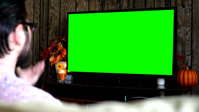Angry millennial male displeased at generic sports game on green screen TV video