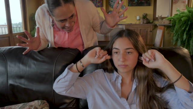 angry mom yelling at her teenage daughter who has her fingers in her ears - rabbia emozione negativa video stock e b–roll