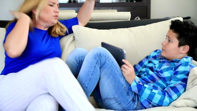stockvideo's en b-roll-footage met boze moeder nemen digitale tablet van zoon - kids online abuse