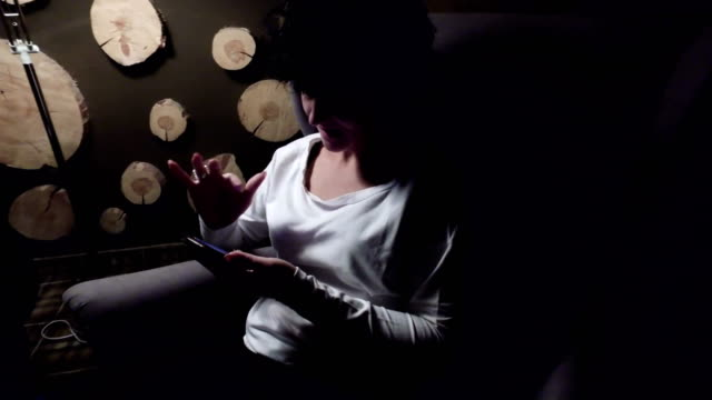 Angry nervous woman hitting the smartphone trying to connect to the internet. Sitting in chair under the lamp in dark atmosphere